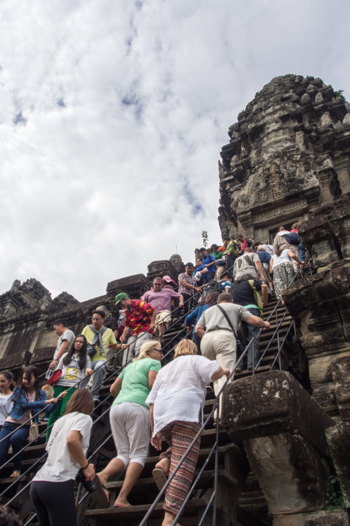 climbing the steps to the top of angkor wat